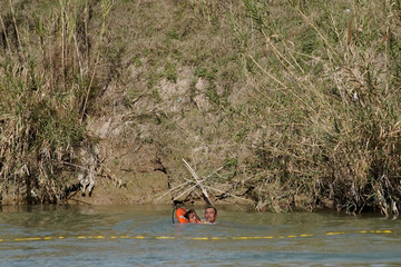 Migrants use a life buoy to get to the banks of the U.S. side of Rio Bravo, as seen from Piedras Negras, Mexico