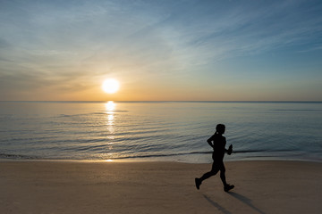 silhouette picture of running on the sand beach during sunrise. healthy and running sport concept