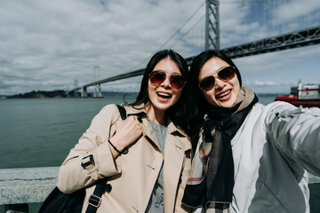 Two joyful cheerful asian girls with sunglasses taking selfie while sightseeing in city having fun. The western section of the San Francisco Oakland Bay Bridge. beautiful ocean view with blue sky.