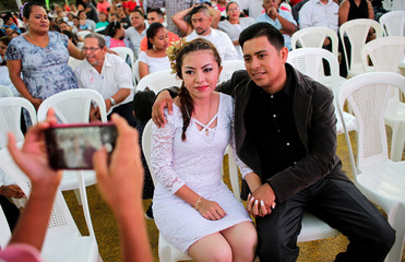 """A newly married couple with scarce financial resources poses for a photo after a free civil ceremony on Valentine's day organized by Sandinista radio """"La nueva radio ya"""" at the Salvador Allende port in Managua"""