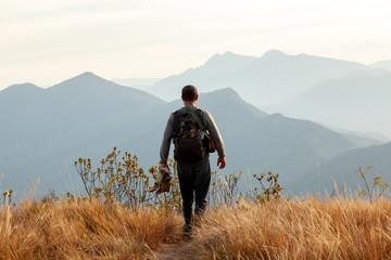 People walking in mountain landscape - trekking hiking mountaneering