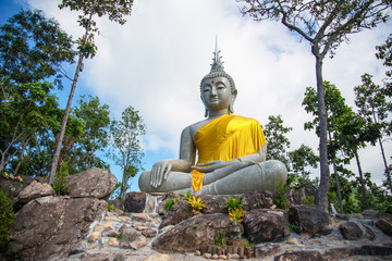 Beautiful big buddha statue sitting on the rock with forest tree and blue sky background