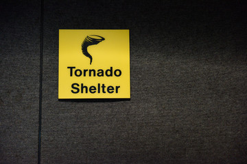 Bright yellow Tornado, or Twister shelter sign, designating a safe room area. With Copy Space.