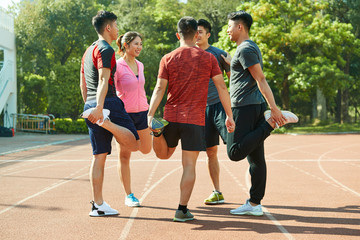 group of young asian athletes stretching legs
