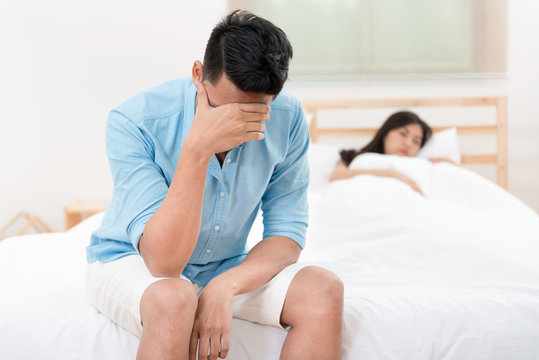Husband unhappy and disappointed in the erectile dysfunction during sex while his wife sleeping on the bed. Sexual Problems in Men.