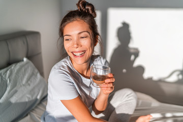 Happy morning Asian woman drinking coffee cup in bed happy chinese casual girl waking up with hot beverage mug relaxing smiling on comfy mattress. Luxury hotel lifestyle relax weekend .