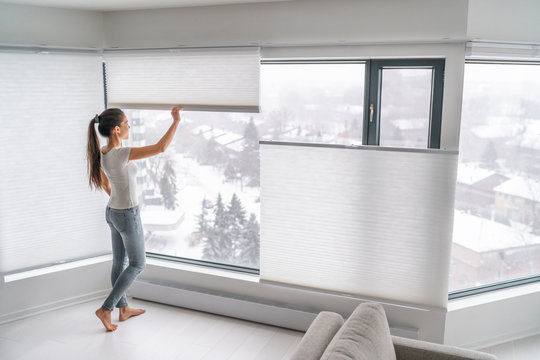 Woman opening home curtains in urban condo. Modern top down bottom up privacy cellular shades on apartment window keeping heat in winter with honeycomb blind curtain. Cordless pleated shades.