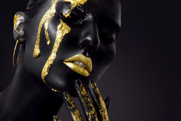 Foto op Plexiglas Fashion Lips Young woman face with art fashion gold makeup. An amazing model with black and gold creative makeup. Closeup portrait
