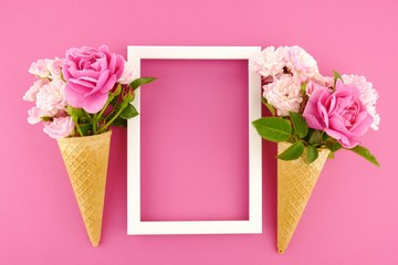 Flower card. Flower frame. Pink roses in an waffle cone and  white  frame on a bright fuchsia background. Flower ice cream.top view,copy space.Mothers Day. International Women's Day.