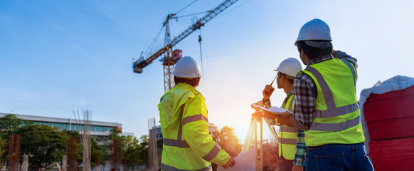 Construction engineers discussion with architects at construction site or building site of highrise building with Surveying for making contour plans is a graphical representation of the lay in land. Wall mural