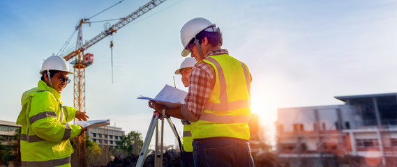 Construction engineers discussion with architects at construction site or building site of highrise building with Surveying for making contour plans is a graphical representation of the lay in land. Fotomurales