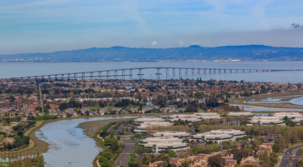 Aerial view from an airplane of San Mateo Hayward bridge across the San Francisco Bay and Foster City in  San Mateo County, California