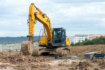Yellow excavator at construction site into mud with sky background