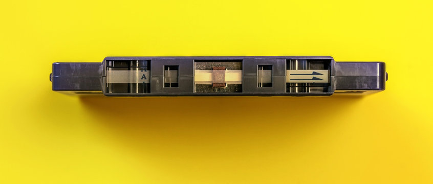 Top down view, start of old audio tape in cassette on yellow board