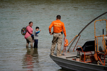 Migrants refuse help from members of the Mexican immigrant welfare agency Grupo Beta to go back to land as they wait to be rescued by a U.S. border patrol boat during their attempt to cross the Rio Bravo towards the United States