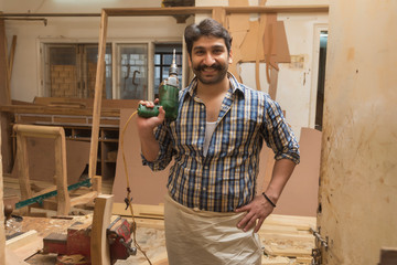 Smiling carpenter posing with a drilling machine standing in his workshop.