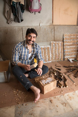 Smiling carpenter making carvings and designs on wood using a chisel in his workshop.