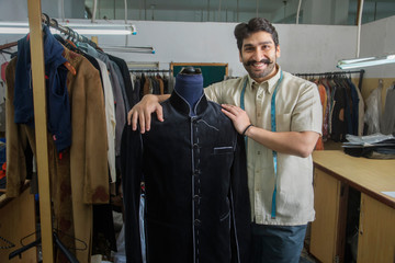 Tailor standing beside a mannequin wearing a semi-stitched coat in his workshop.
