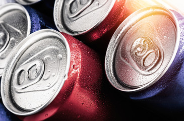 Red and blue cans of soft drinks with water drops.