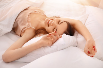 Morning of beautiful young woman lying in bed