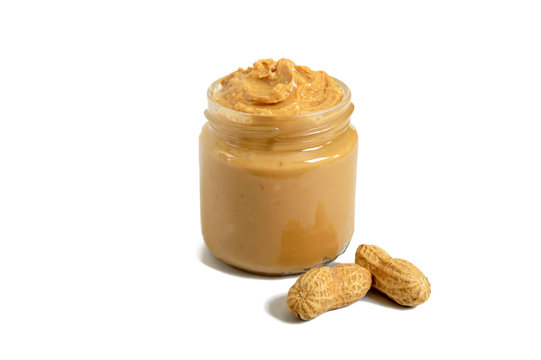 Peanut butter in a glass jar with peanuts isolated on white background.  A traditional product of American cuisine.