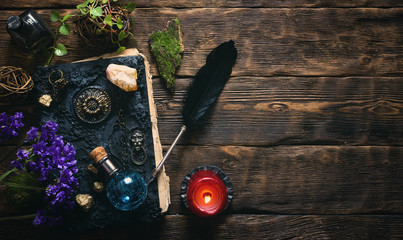 Spell book, magic potions and other various witchcraft accessories on the wizard table background with copy space. Fotoväggar