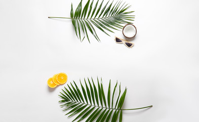 Female sunglasses with tropical fruits and leaves on white background