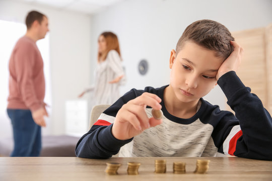 Sad little boy with coins and his quarreling parents at home. Concept of child support