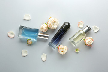 Bottles of perfume and flowers on light background