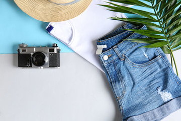 Summer composition with clothes and photo camera on white background
