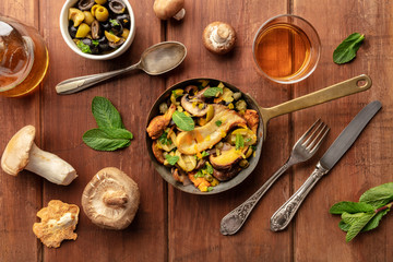 An overhead photo of a rustic mushrooms and olives saute with mint, with a glass of white wine