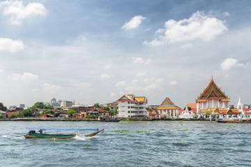 Boat sailing along the Chao Phraya River in Bangkok, Thailand