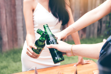 Close up young asian people holding beer bottles and clink with drinking together.