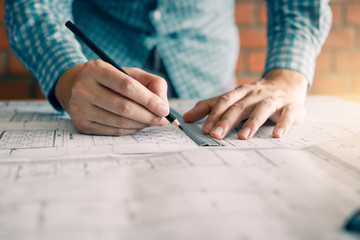 Engineering or architect reviewing blueprints and holding pencil on desk at home office.