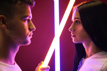 Portrait of young couple with neon lamps on color background