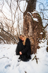 Depressed and lonely woman crying in forest in winter