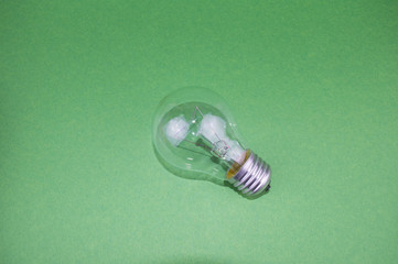 incandescent bulb on a green background, there is an empty space to fill