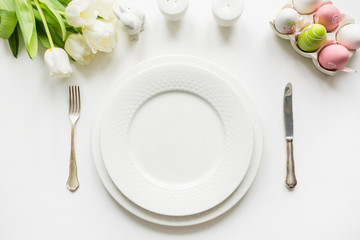 Easter dinner. Table setting with white tulip on white table. Top view.