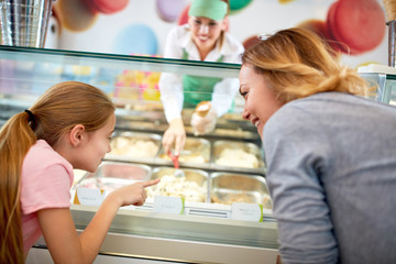 Mother and daughter chooses ice cream in confectionery