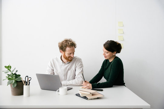 A thirty something couple is working on a laptop in a clean white empty office setting.