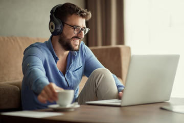 man uses a laptop to listen to music and relax at home.