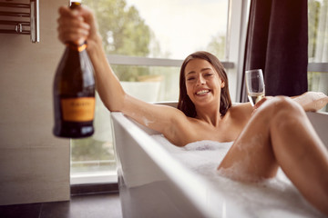 Smiling girl relaxing in bath with foam and drink champagne.
