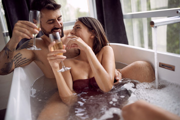 Sexy man and woman have fun together in the bathtub and drinking champagne.