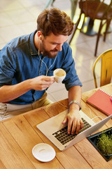 Male working at laptop and drinks coffee.