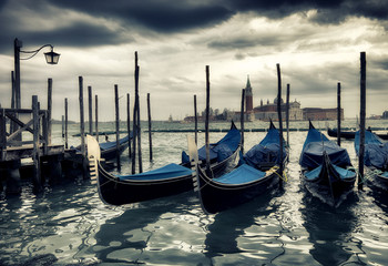 Foto op Canvas Gondolas Gondolas with San Giorgio Maggiore Church on background. Vignetted and grained for the mood.
