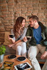 Couple talking and drinking aromatic coffee in cafeteria