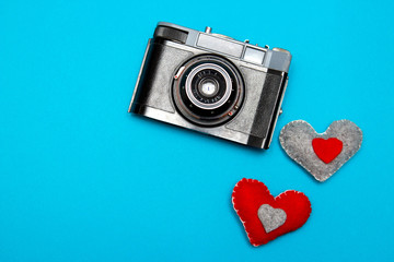 vintage camera on blue background with two felt hearts.