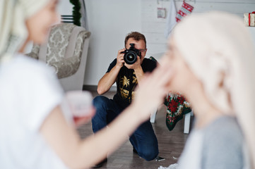 Man photographer shooting on studio two girls while they make their own masks cream. Professional photographer on work.