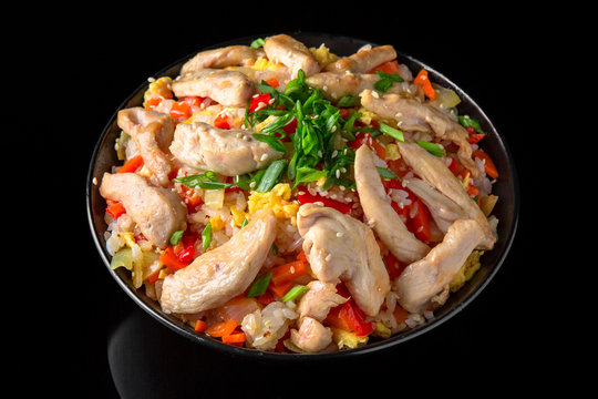 A plate of delicious rice with chicken in sauce and vegetables: carrots, sweet peppers, greens, spices on a black background
