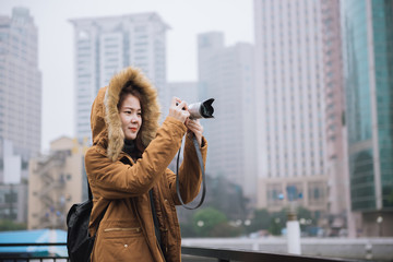 Shanghai travel. Young woman traveler taking photo picture at big city in china. Young asian woman in jacket clothes using camera take a picture of city in shanghai.
